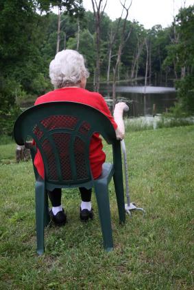 senior lady sitting and holding walking stick