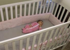 Baby in crib with bumper