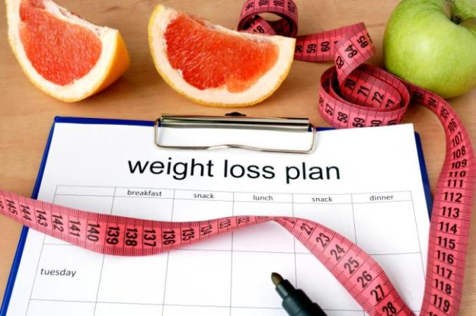 Clipboard with a weight loss plan, measuring tape and fruit.