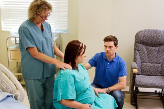 A woman in labor with doctor and partner.
