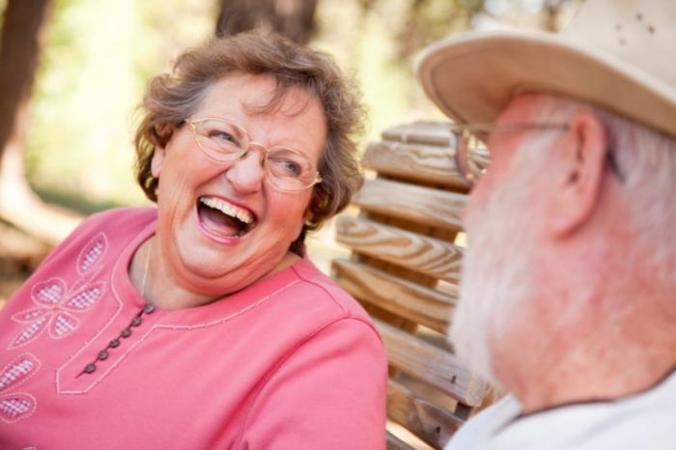 older woman laughing talking to older man